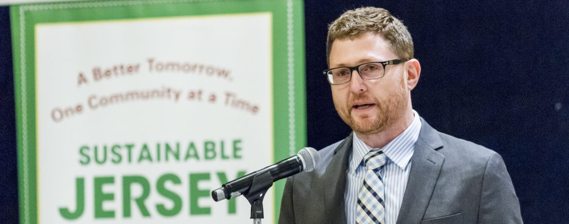 Sustainable New Jersey Randall Solomon, Executive Director, speaking at a podium with a Sustainable Jersey poster behind him.