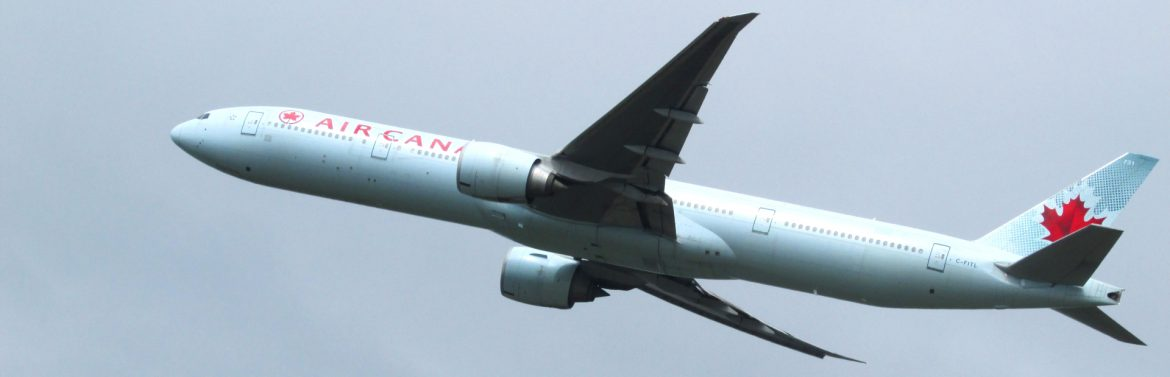 Air Canada commercial jet flying in the sky.