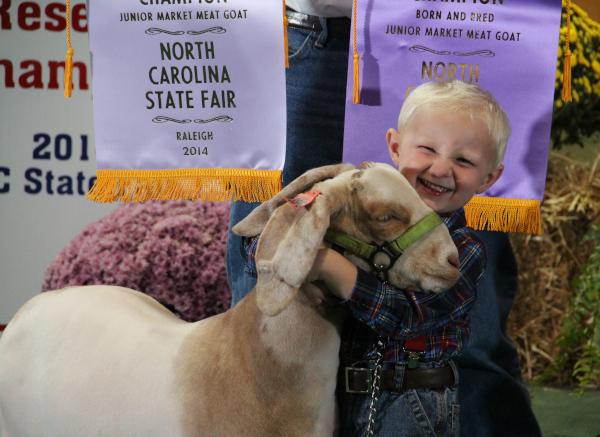 North Carolina State Fair, a boy smiles hugging an animal.
