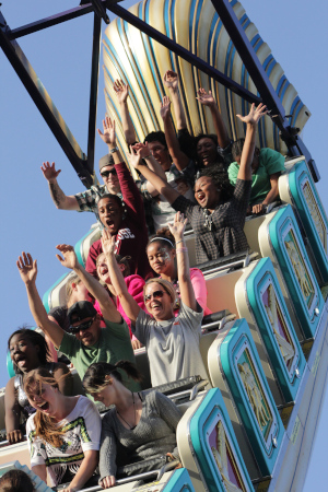 North Carolina State Fair, a group of people with their arms up and screaming going downwards on a roller coaster.