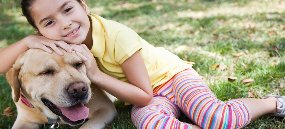 Pethealth; A girl laying on top of a dog in the grass.