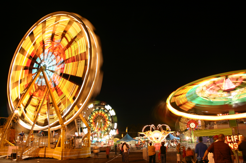 Tyler, Texas east texas fair ferris wheel and other rides lit up at night.
