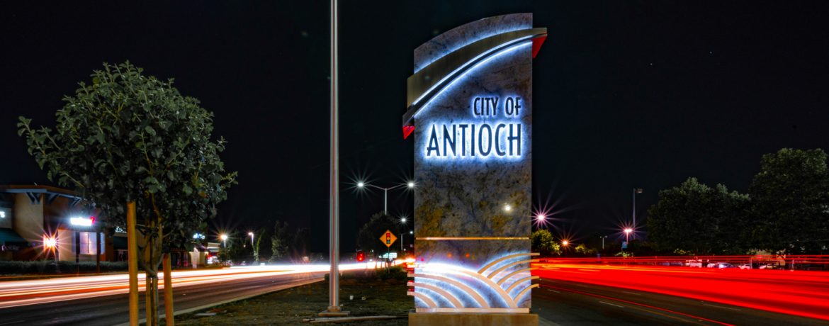 Antioch, California welcome sign at night with time laps headlights and taillights showing as streaks of light.