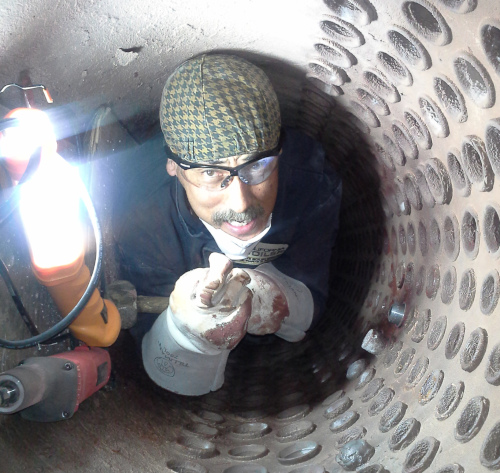 California Boiler employee crawling inside of a tight space while working.