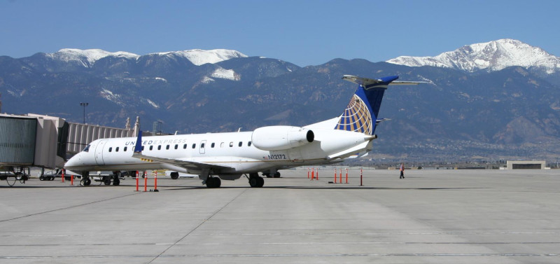 The Colorado Springs Airport, a commercial jet at the terminal building with mountains behind.