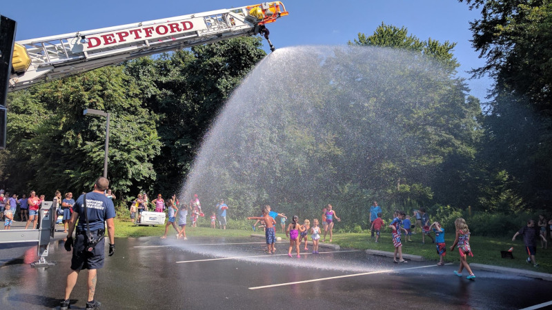 Deptford Township, New Jersey fire department spraying water on kids from a ladder.