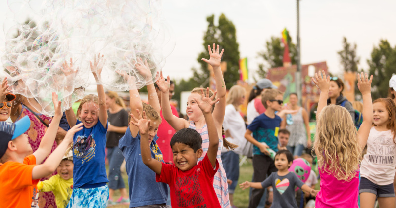 Dublin, California kids with large bubbles in the air and their eyes closed with hands up to pop them.
