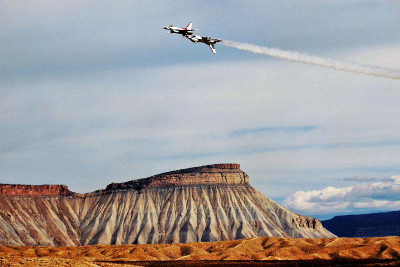 Grand Junction Regional Airport jets in the air doing a stunt with mountain in the background.