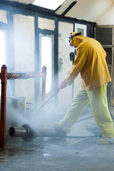 UniTech Services Group employee spraying a part in hazmat gear.