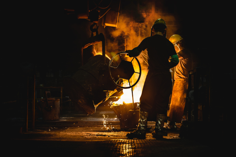 The Buck Company employees pouring molten metal.