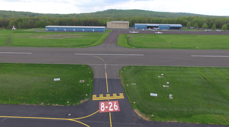 Pennridge Airport Runway from 8-26 showing hangars and small craft in the distance.