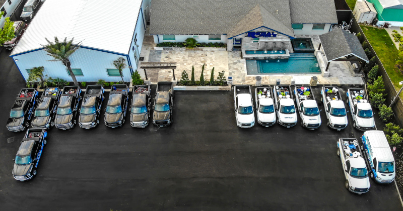 Regal Pools office building aerial view with work vehicles parked out back.
