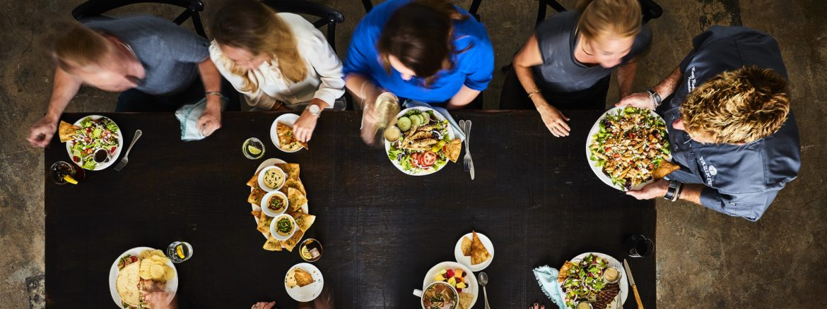 Taziki's Mediterranean Café community table view from above with a waiter serving people at a table.
