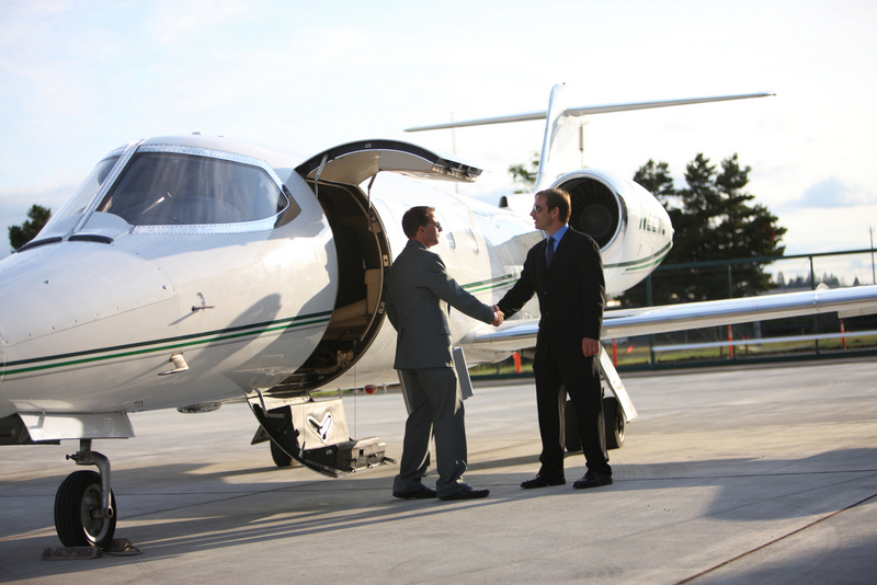 Texarkana Regional Airport corporate jet with two men in suits shaking hands.