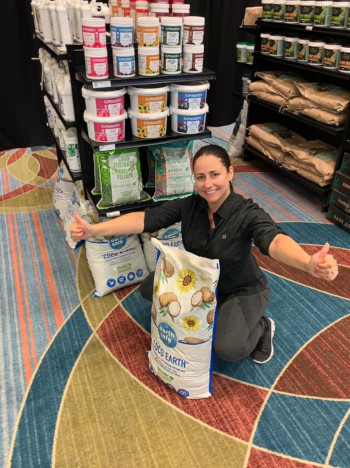 Greenstar Plant Products Inc. ; a woman in a store with a product bag on the ground, she is kneeling with her arms stretched open.