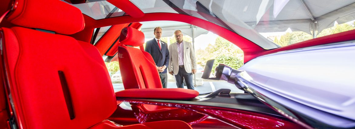 Peachtree Corners, Georgia two men looking at a high tech automobile with red seats.