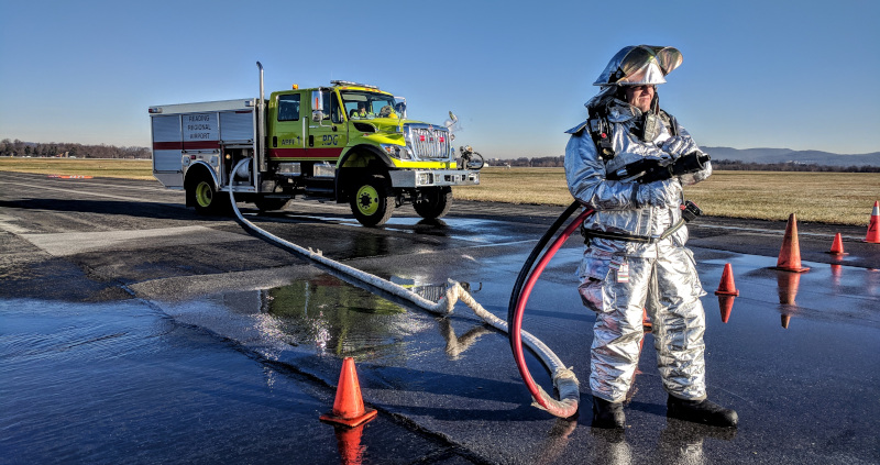Reading Regional Airport man in a fireproof suit on the runway with a host and truck.