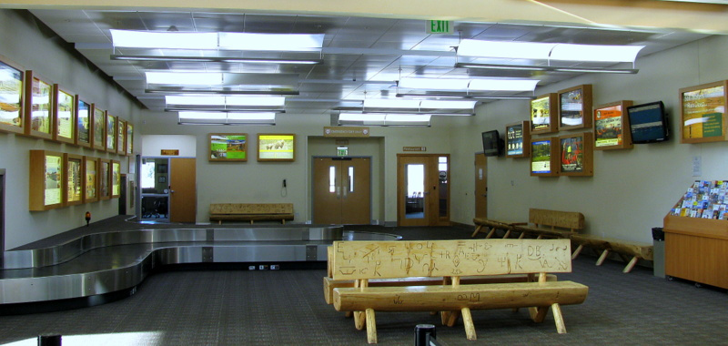 Yellowstone Regional Airport Cody Wyoming, terminal interior showing baggage claim and a wood bench made of logs with carvings in it
