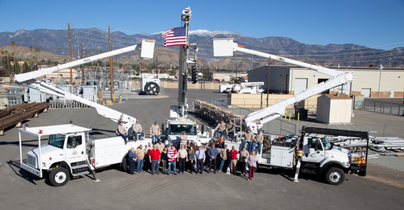Banning, California Banning Electric Department vehicles and people posing for a group photo with an american flag on one of the vehicles booms in the air.