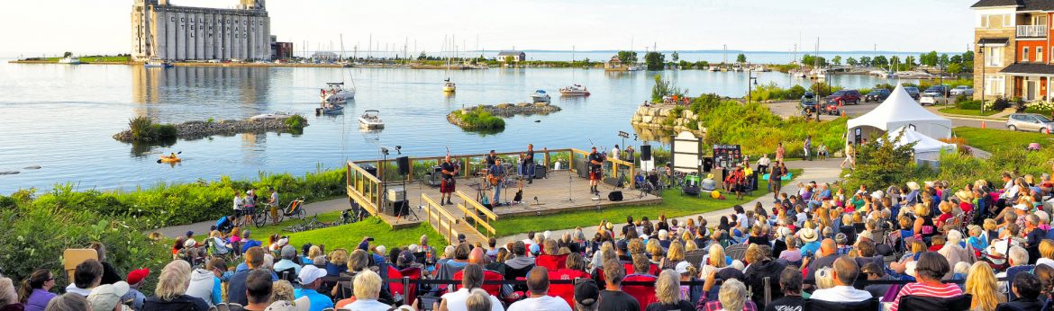 Collingwood, Ontario event with a crown sitting watching musicians along the water.
