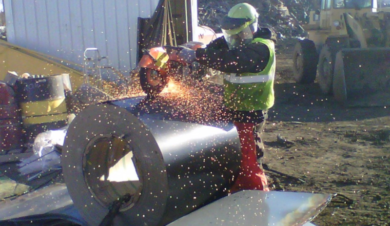 M. Gervich & Sons, Inc. employee using a demo saw on a roll of metal sheets.