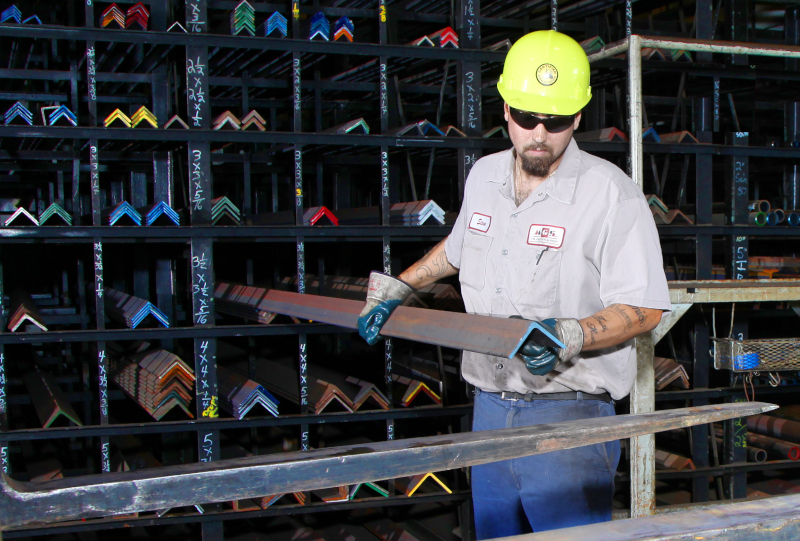 M. Gervich & Sons, Inc. employee grabbing a metal bar from a rack.