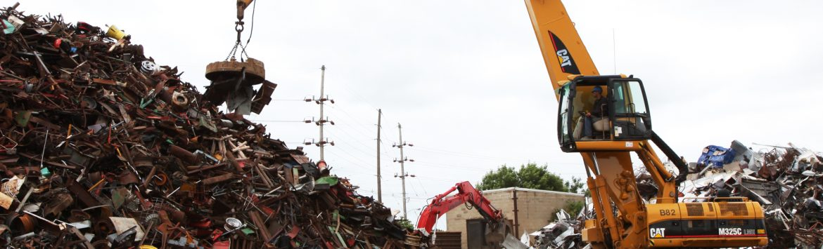 M. Gervich & Sons, Inc. crane with magnet moving scrap metal from a pile.