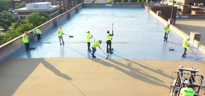 RAM Construction Services applying product on a rooftop with a group of men working.