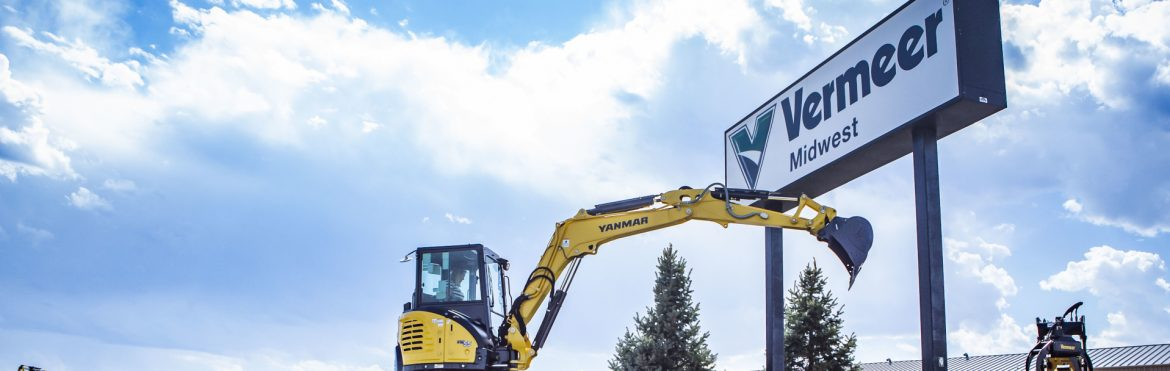 Vermeer Midwest sign and a woman operating a Vermeer excavator next to it.