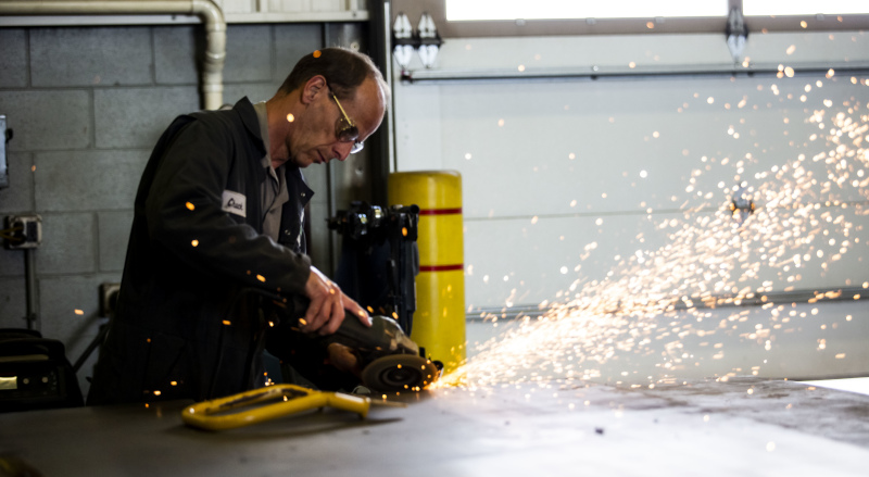 Vermeer Midwest employee grinding a part with sparks flying.