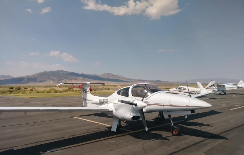 Winnemucca Municipal Airport airplanes on runway with mountains and sky behind.