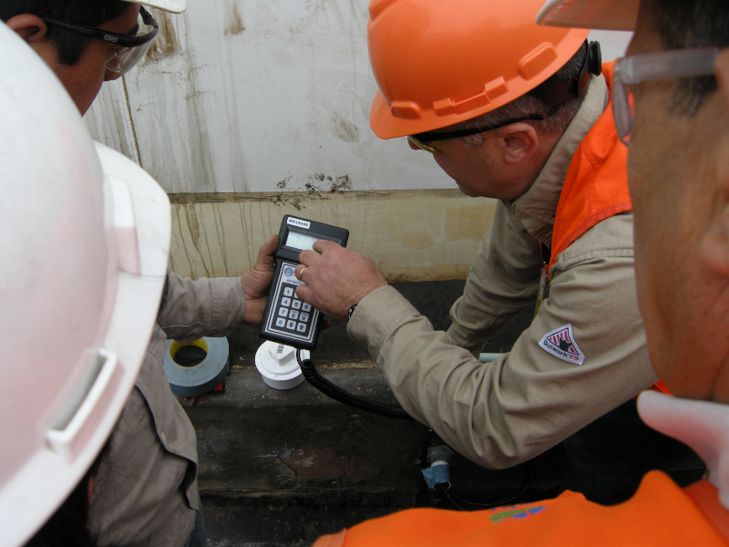 Zerust Oil & Gas workers looking at a readout on an instrument in the field.