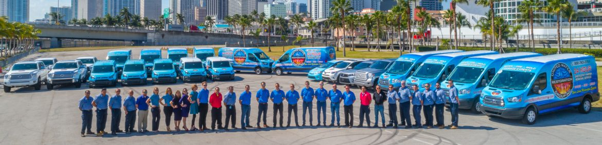 United Water Restoration Group, Inc. employees lined up in front of work vehicles for a photo.