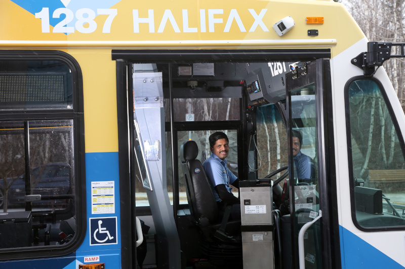 Halifax Transit bus employee with the bus door open smiling.