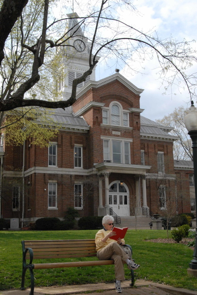 Simpson County, Kentucky courthouse with a person reading out front on a bench.