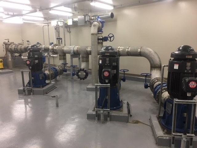 Warman, Saskatchewan new pump house interior with pumps mounted on cement floor.