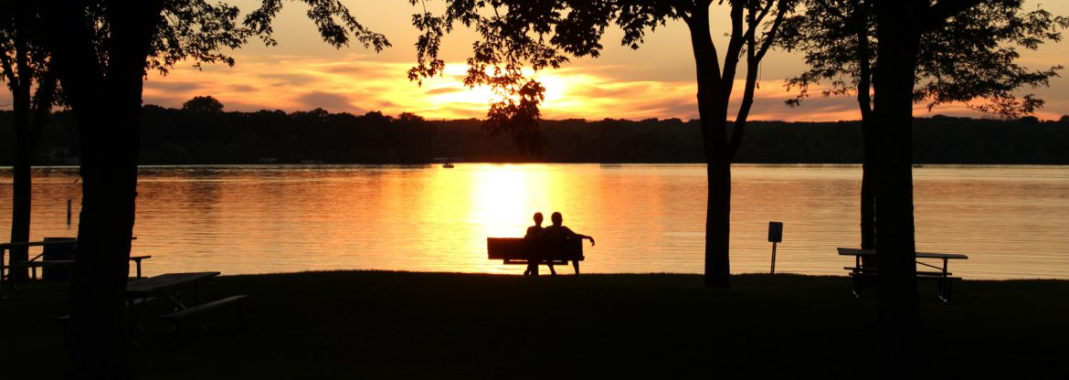 Lakeville, Minnesota Antlers park sunset with dark black foreground shapes and a bench with two adults sitting in front of the suns reflection on the water.