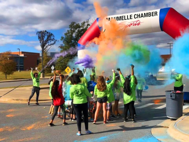 Maumelle, Arkansas event with colorful powder being thrown into the air.