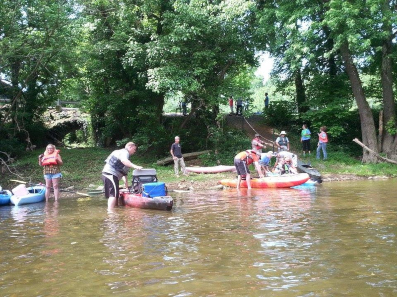 Adair County, Kentucky trail town with people on the shore and kayaks in the water.