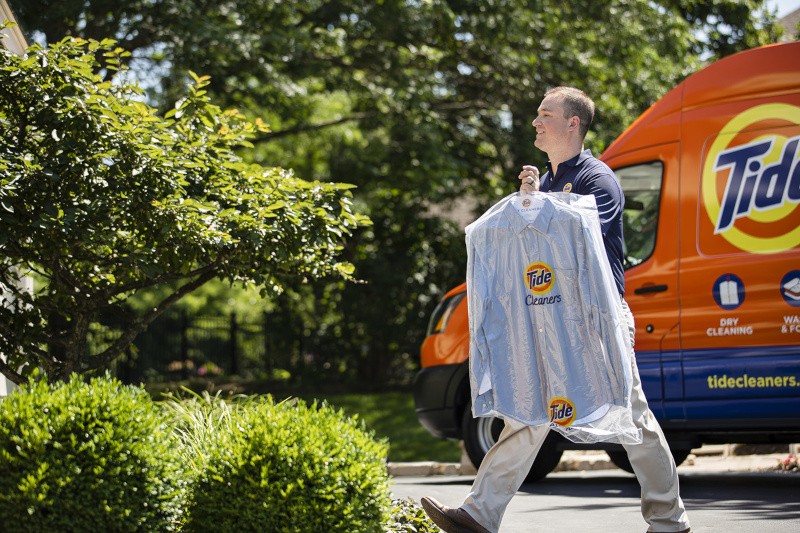 Tide Cleaners. A man walking away from a Tide Cleaners van with clean clothing on a hanger.