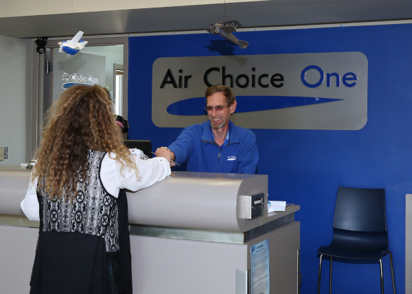 Mason City Municipal Airport MCW Air Choice counter with employee and customer.