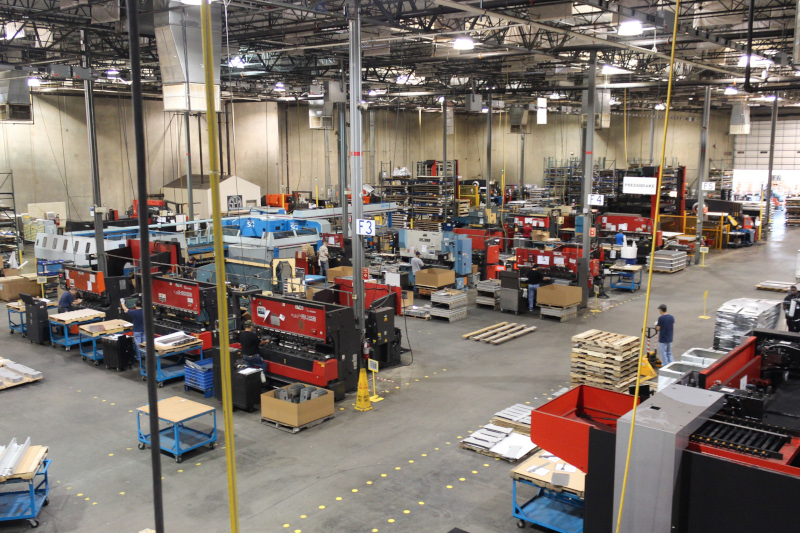 Special Products & Mfg., Inc. interior warehouse view showing work stations and people working.