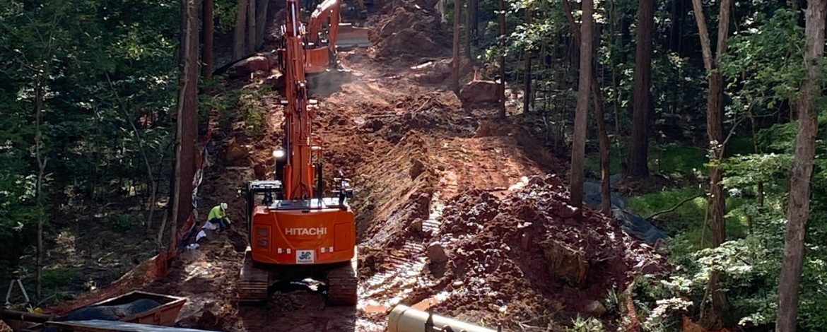 J.F. Wilkerson Contracting Company, Inc. excavators on a hillside with trees around.