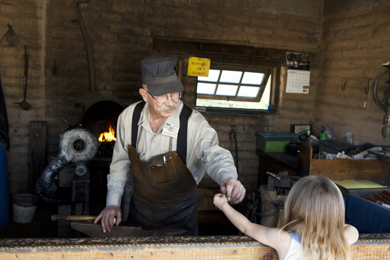 Las Cruces, New Mexico Farm Ranch Museum showing a man dressed in period attire interacting with a young woman.