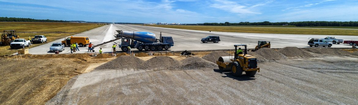 Oscoda-Wurtsmith Airport OWA runway construction with work vehicles and people present