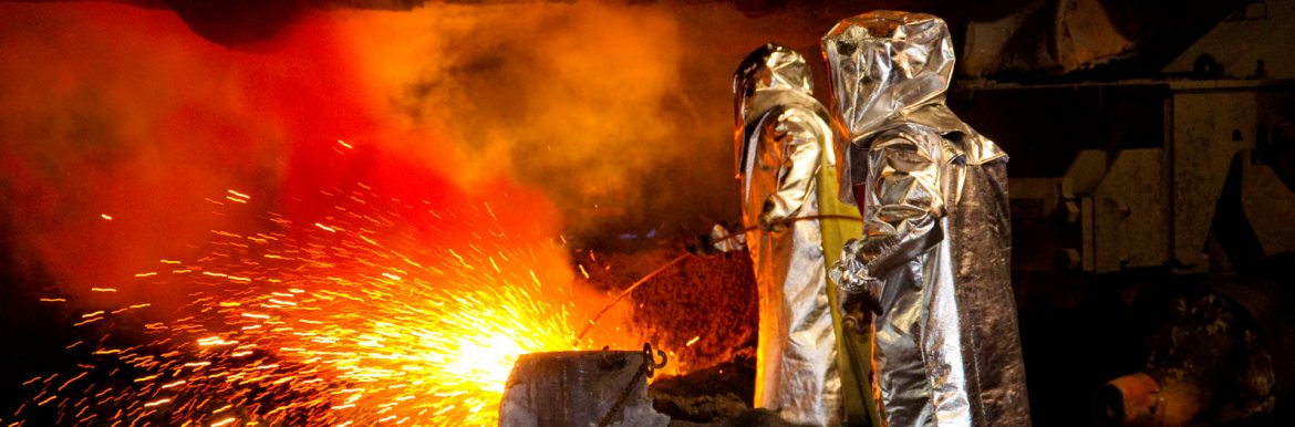 American Iron and Steel Institute workers in protective gear working with hot sparking metal.