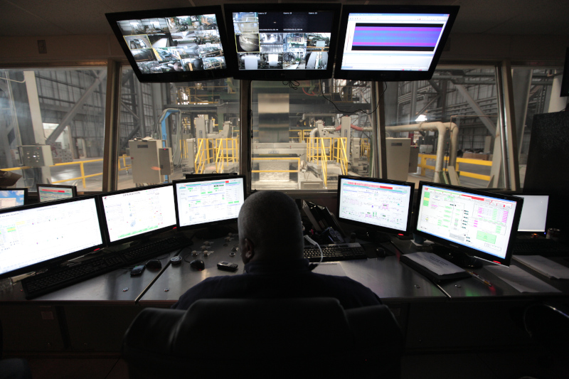 American Iron and Steel Institute. A person in a room with monitors overlooking production area.