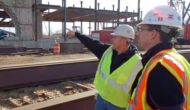 Pioneer Construction employees talking and pointing at a construction site.