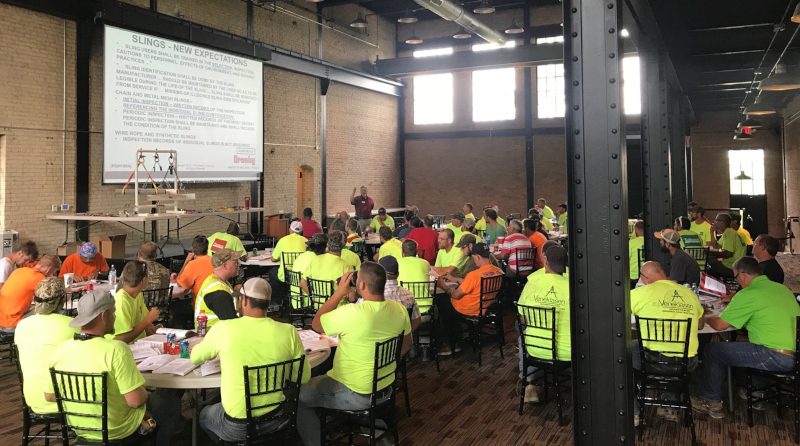 Pioneer Construction employee training with people sitting at tables with a screen showing information.