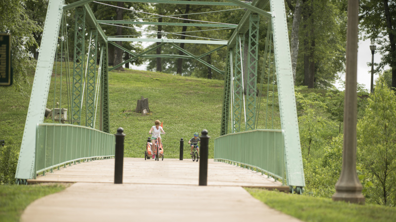 Trussville, Alabama truss bridge with a woman and child riding on bikes across.